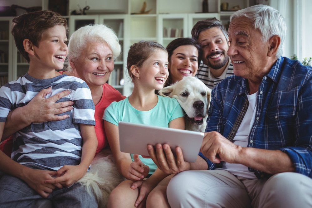 Happy multi-generation family using digital tablet in living room at home.jpeg